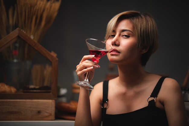 Garota asiática sexy segurando taças de vinho tinto