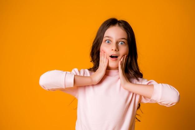 Garota assustada ou surpresa com as mãos no rosto