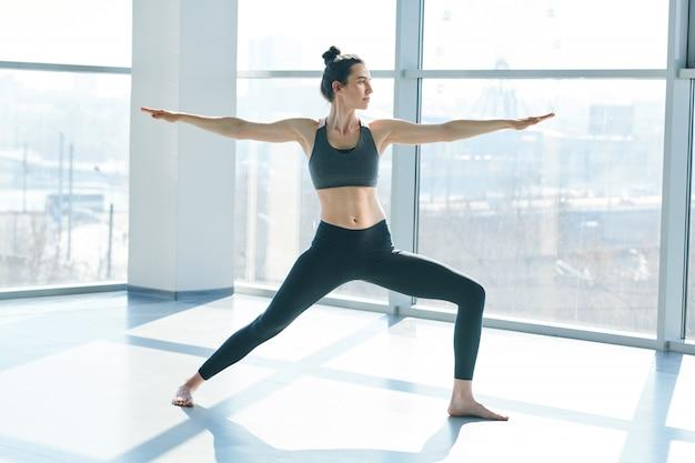 Garota ativa em forma com leggins pretas e top de pé no chão em posição de ioga com os braços estendidos durante o treino