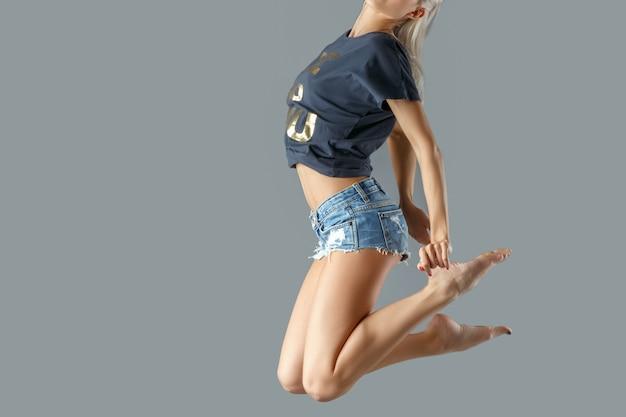 Garota ativa esportiva em movimento pulando no ar.