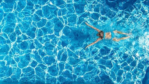 Garota ativa na vista aérea de zangão piscina de cima, jovem mulher nada na água azul, férias tropicais, férias no conceito de resort