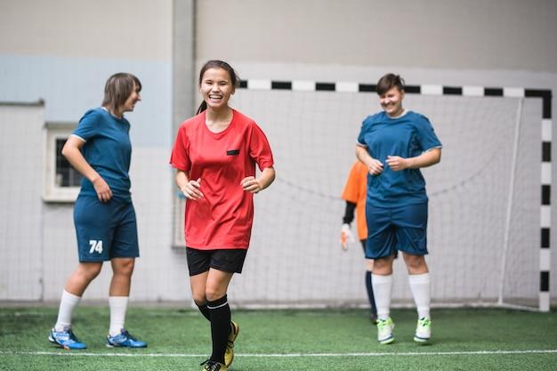 Garota ativa rindo em uniforme esportivo correndo por um campo de futebol verde