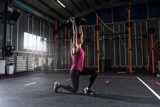 Garota atlética determinada treina na academia com um disco de barra