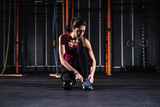 Garota atlética determinada treina na academia com um kettlebell