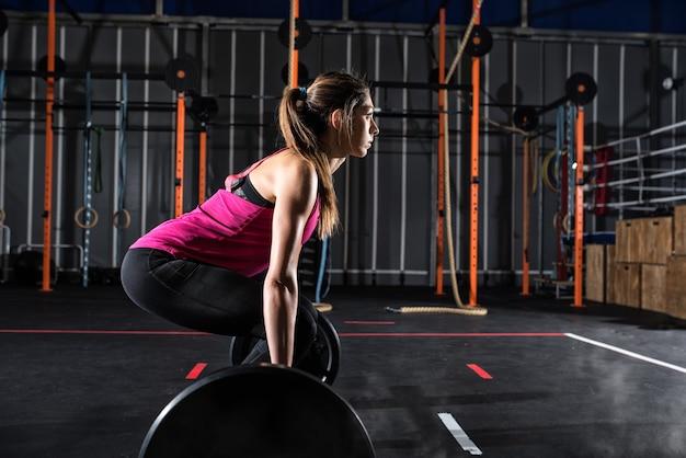 Garota atlética determinada treina na academia com uma barra