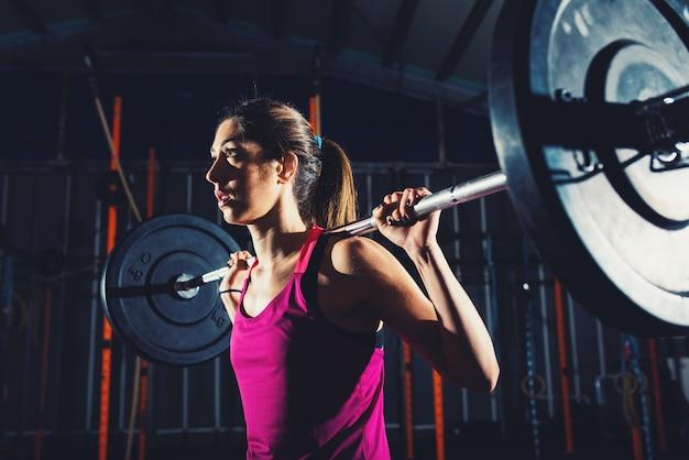 Garota atlética malhando na academia com uma barra