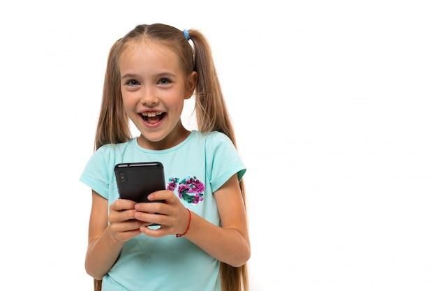 Garota atraente adolescente em roupas casuais varas em um smartphone em um fundo branco, com espaço de cópia