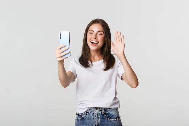 Garota atraente amigável dizendo oi, acenando com a mão no smartphone durante a videochamada, tendo uma conversa.