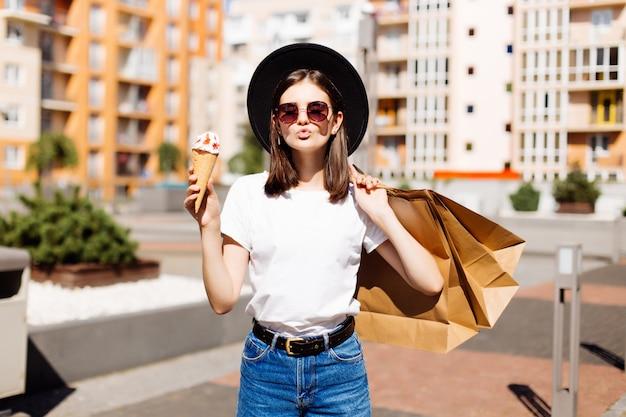 Garota atraente, andando com sorvete segurando sacolas de compras no shopping