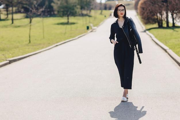 Garota atraente, andando na estrada do parque em dia de sol