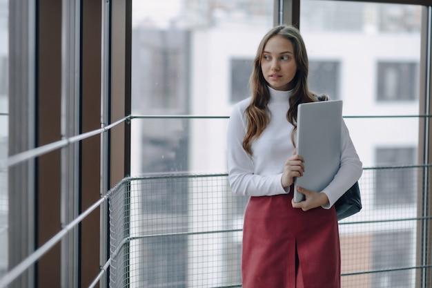 Garota atraente caminha em um corredor brilhante com laptop e coisas no terminal do aeroporto ou escritório. atmosfera de viagem ou ambiente de trabalho alternativo.