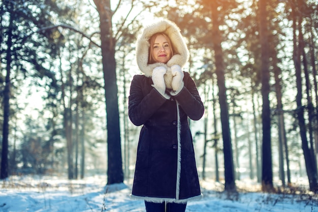 Garota atraente caminha na floresta de inverno entre as árvores