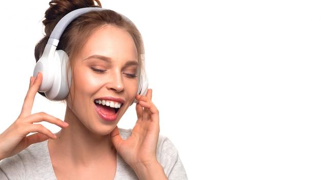 Garota atraente, cantando com fones de ouvido