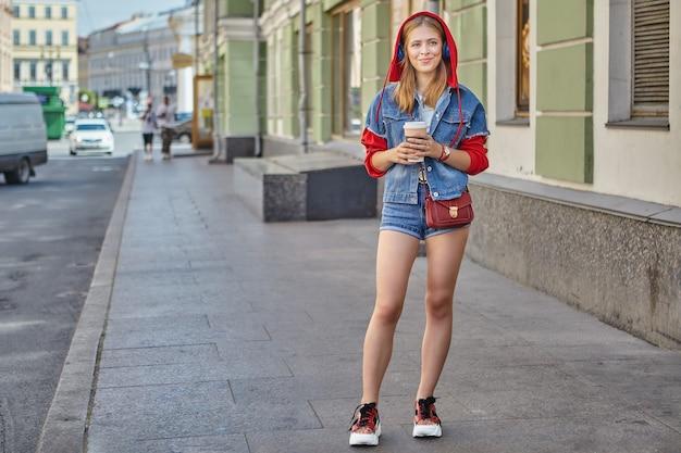 Garota atraente caucasiana, cerca de 20 anos de casaco com capuz vermelho e shorts está andando durante a rua.