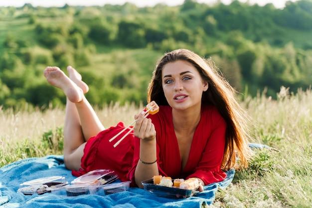 Garota atraente com 3 conjuntos de sushi coloca na capa azul em colinas verdes.