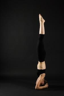 Garota atraente com blusa azul fazendo ioga com apoio de cabeça em fundo preto