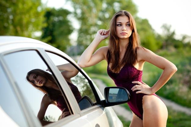 Garota atraente com cabelo castanho, na cueca roxa, posando de pé perto de um carro branco. foto ao ar livre com fundo desfocado