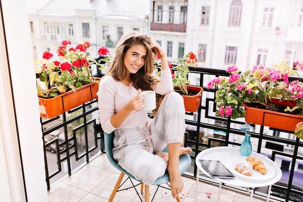 Garota atraente com cabelo comprido de pijama, tomando café da manhã na varanda pela manhã na cidade. ela segura uma xícara e está sorrindo.
