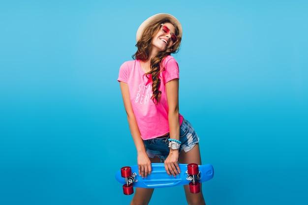 Garota atraente com cabelo longo cacheado no chapéu, posando em fundo azul no estúdio. ela usa shorts, camiseta rosa, óculos de sol rosa. ela segura o skate azul.