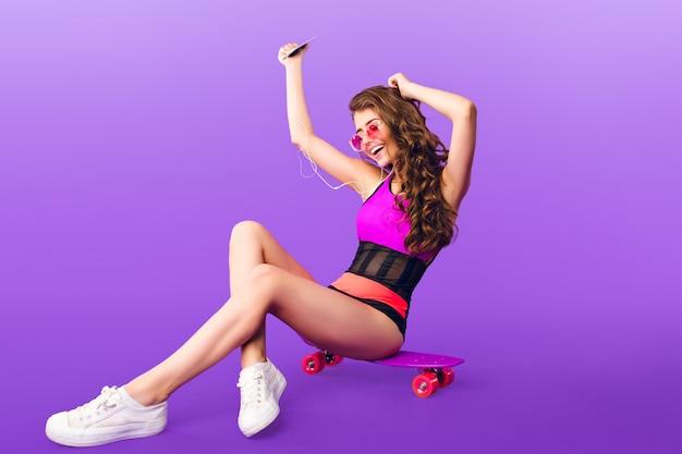 Garota atraente com cabelo longo encaracolado em óculos de sol rosa, sentado no skate sobre fundo roxo. ela usa maiô e escuta música energética com fones de ouvido.