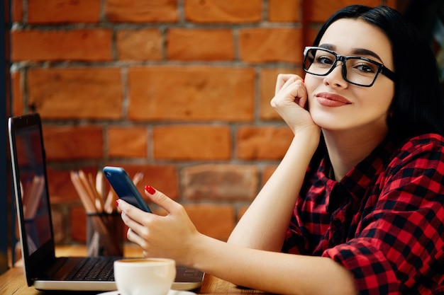 Garota atraente com cabelo preto, usando óculos, sentado no café com laptop, telefone celular e xícara de café, conceito freelance, retrato, cópia espaço, camisa vermelha.
