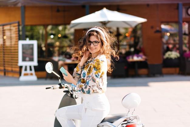 Garota atraente com incríveis cachos castanhos relaxando na rua principal da cidade com uma cafeteria