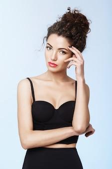 Garota atraente com maquiagem brilhante posando sobre parede azul