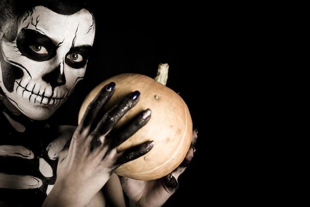 Garota atraente com maquiagem esqueleto detém uma abóbora