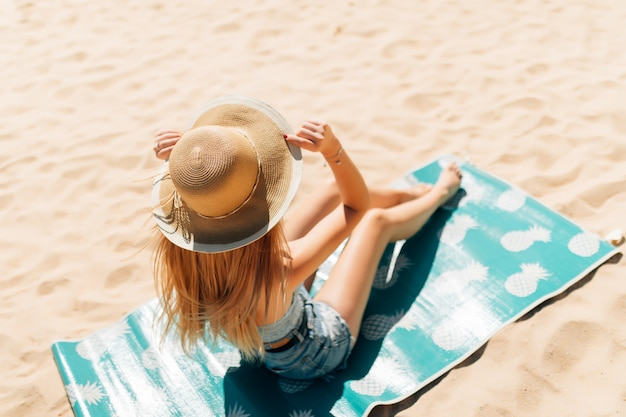 Garota atraente com óculos escuros e chapéu deitada na areia quente