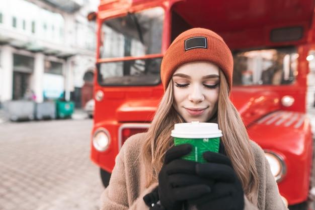 Garota atraente com roupas quentes em pé na rua, segurando um copo de papel de café na mão