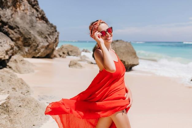 Garota atraente com sorriso feliz andando pela costa do oceano. modelo feminino refinado em vestido vermelho e óculos de sol relaxantes na praia em um dia ensolarado.