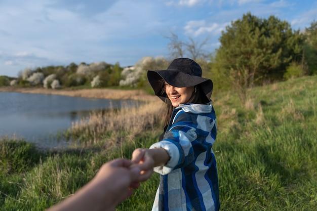 Garota atraente com um chapéu ao pôr do sol em uma caminhada à beira do lago