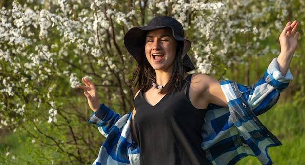 Garota atraente com um chapéu entre as árvores floridas, na primavera, em um estilo casual.