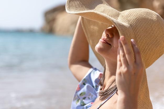Garota atraente com um chapéu esconde o rosto do sol, sentada à beira-mar.