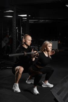 Garota atraente com um personal trainer malhando em uma academia. fazendo agachamentos com barra de barra.
