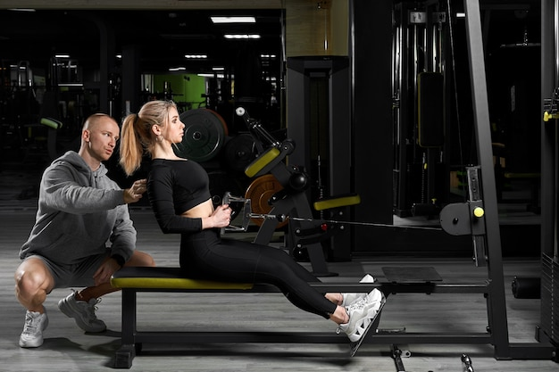 Garota atraente com um personal trainer malhando em uma academia. instrutor de fitness realiza treinamento pessoal.