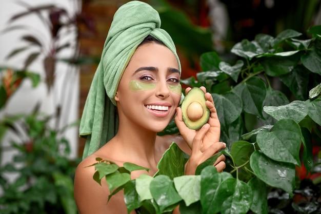 Garota atraente com um sorriso branco como a neve depois do banho posa com um abacate nas mãos