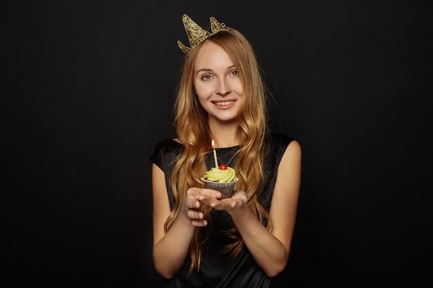Garota atraente com uma coroa e cupcake