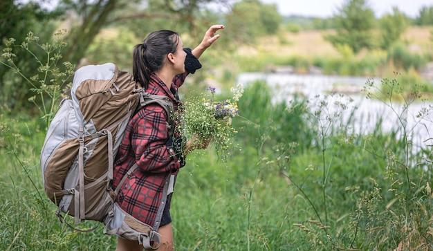 Garota atraente com uma grande mochila de viagem e um buquê de flores silvestres.