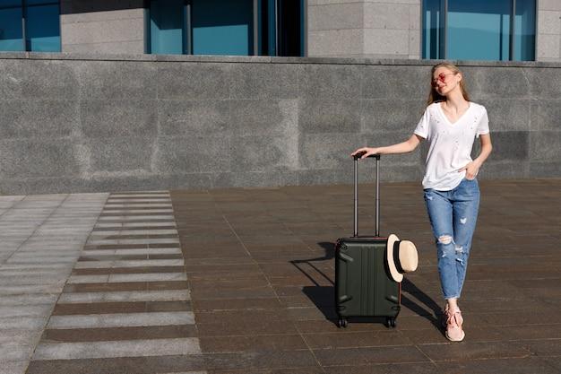 Garota atraente com uma mala fica de pé e espera o ônibus no verão