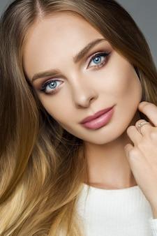 Garota atraente com uma pele impecável e maquiagem perfeita, olhando para a câmera.