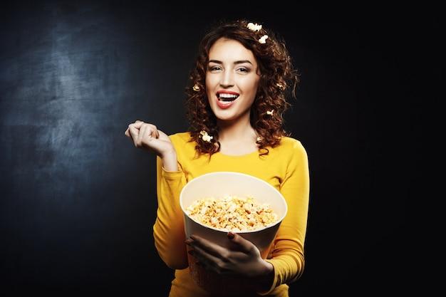 Garota atraente, comendo saborosa pipoca doce salgada, assistindo programas de tv
