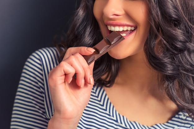 Garota atraente, comer chocolate e sorrindo.