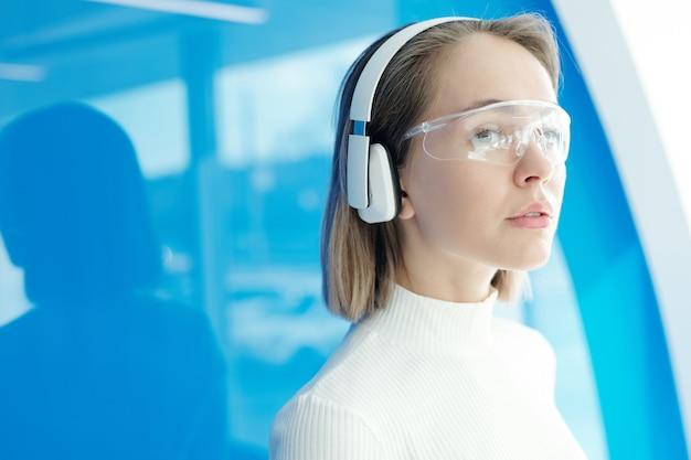 Garota atraente contemplativa com fones de ouvido sem fio e óculos inovadores trabalhando em um escritório moderno