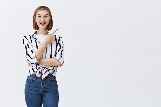 Garota atraente curiosa e intrigada mostra uma promoção interessante apontando para o canto superior direito
