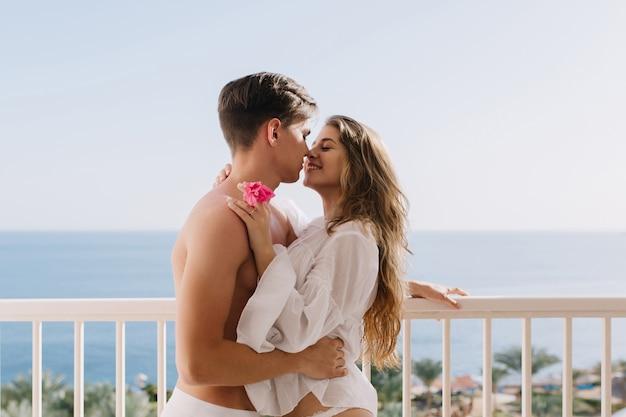 Garota atraente de cabelos compridos com flor rosa na mão, tocando suavemente o jovem moreno e olhando em seus olhos. rapaz com um penteado moderno a abraçar a sua namorada encantadora e a beijá-la