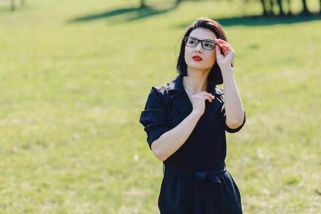 Garota atraente de fato no fundo da grama verde