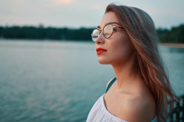 Garota atraente de óculos no parque vista para o lago
