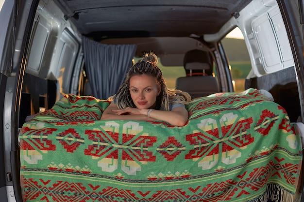 Garota atraente deitada em sua minivan em um cobertor verde brilhante e olha diretamente para a câmera ...