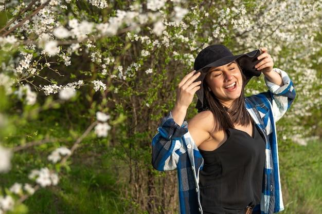 Garota atraente e alegre com um chapéu entre as árvores floridas, na primavera, em um estilo casual.